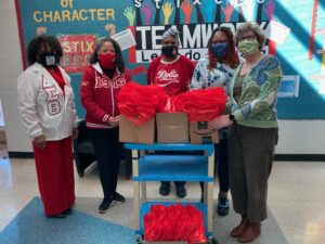 Delta Sigma Theta Sorority, St. Louis Alumnae Chapter posing in classroom with delivered books for students